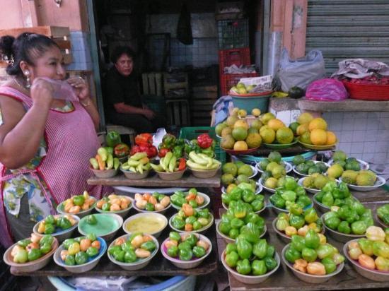 Assortiment de chiles et derrière à droite les limas et oranges amères.