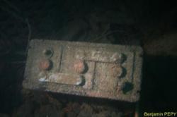 Une batterie visible au milieu des restes de la timonerie